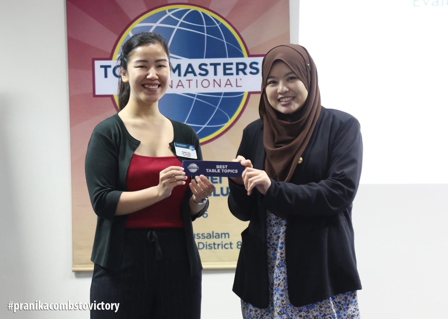 Pranika (left) receives Best Table Topics Ribbon from Awfa (right)